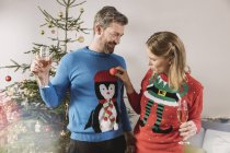 Two people with ugly Christmas sweaters laughing in front of christmas tree — Stock Photo