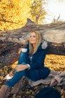 Donna sorridente che tiene la tazza nella foresta autunnale — Foto stock