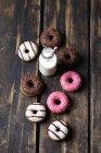 Frasco de vidro de leite e donuts com diferentes coberturas em madeira escura — Fotografia de Stock
