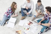 Colleagues in office sitting on floor with photo prints — Stock Photo