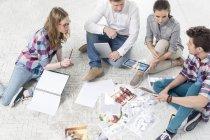 Коллеги в офисе, сидя на полу с фото печать — стоковое фото