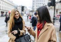 Zwei Freunde, die Stadt zu erkunden und mit Smartphone, London, Uk — Stockfoto