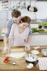 Affectionate couple preparing pizza dough in kitchen — Stock Photo