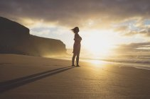 Spain, Fuerteventura, Woman standing on the beach at sunset — Stock Photo
