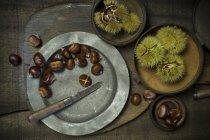 Вид сверху сладкие каштаны в миски и на табличке с ножом — стоковое фото
