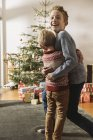 Two brothers hugging in front of Christmas tree and looking at presents — Stock Photo