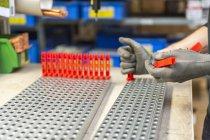 Trabalhador colocando produtos plásticos na montagem — Fotografia de Stock