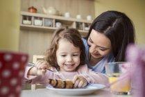 Kleine Mädchen und Mutter frühstücken — Stockfoto