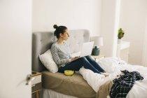 Femme assise dans son lit et à l'aide d'ordinateur portable — Photo de stock