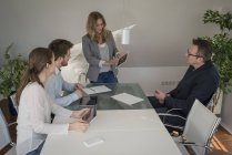 Woman leading a presentation with digital tablet in conference room — Stock Photo