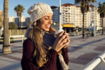 Spain, Andalusia, Cadiz, El Puerto de Santa Maria, woman in winter clothes drinking coffee — Stock Photo