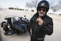 Portrait of cool biker wearing helmet and sunglasses standing on a road in front of his sidecar motorcycle — Stock Photo