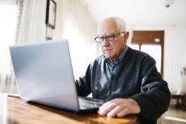 Uomo anziano usando il portatile — Foto stock