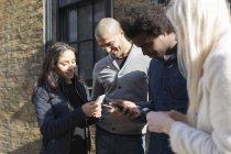 Amis heureux en utilisant des téléphones cellulaires en face du bâtiment en brique — Photo de stock