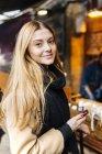 Giovane donna in possesso di smartphone e guardando in fotocamera sulla strada — Foto stock
