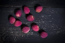 Fresh unpeeled Lychees on dark wood — Stock Photo