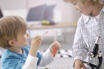 Due ragazzini che giocano con gli utensili di laboratorio chimico — Foto stock