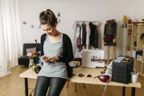 Молодий моди дизайнер працюють в її студії, за допомогою смартфона — стокове фото