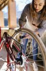 Young smart woman repairing her bicycle — Stock Photo