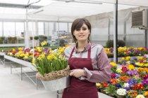 Female gardener holding flowerpot — Stock Photo