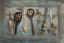 Row of spoons and shovels with different sorts of nuts on wood — Stock Photo