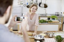 Hombre tomando foto de celular de mujer sonriente preparar pasta en cocina - foto de stock