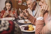 Члены семьи, играя с их смартфонов после Рождественский ужин — стоковое фото