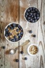 Bowls of porridge with blueberries on wooden surface — Stock Photo