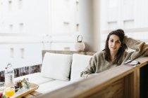 Портрет женщины, отдыхающей на балконе, смотрящей в камеру — стоковое фото