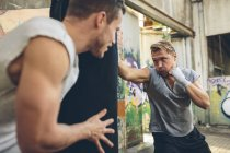Boxers exercising at punch bag in building with graffiti — Stock Photo