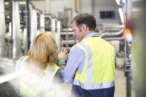 Коллеги в светоотражающих жилетах говорят на промышленном предприятии — стоковое фото