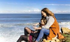 Две молодые женщины, весело с смартфон на берегу моря — стоковое фото