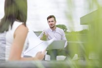 Young businessman and woman having a business meeting on rooftop terrace — Stock Photo