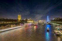 Reino Unido, Londres, vista al río Támesis con el Palacio de Westminster y London Eye por la noche - foto de stock