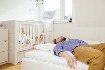 Pai exausto, deitada na cama — Fotografia de Stock