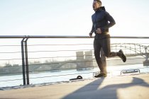 Young man running at the riverside — Stock Photo