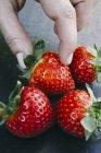 Weibliche Finger unter Erdbeere — Stockfoto