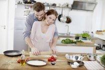 Cariñosa pareja preparando la masa de pizza en la cocina - foto de stock