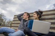 Happy teenage couple sitting outdoors with laptop and headphones — Stock Photo