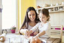 Little girl and mother rolling out dough — Stock Photo