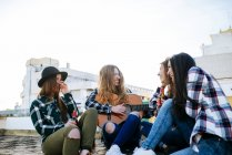 Donna che suona la chitarra su una terrazza sul tetto mentre gli amici ascoltano — Foto stock