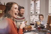 Happy woman pulling Christmas cracker at family table — Stock Photo
