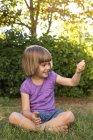 Улыбающаяся маленькая девочка сидит на лугу и смотрит на что-то в руке. — стоковое фото