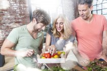 Amis dans la cuisine en regardant caisse avec tomates — Photo de stock