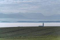 Igreja da Áustria, Ostermiething, no nevoeiro, montanhas ao fundo — Fotografia de Stock