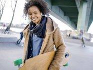Jeune femme souriante avec musique d'audition de longboard avec écouteurs — Photo de stock