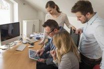 Чотири колегами в офісі обміну цифровий планшетний — стокове фото