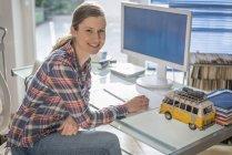 Портрет усміхнений молода жінка на столі в офісі — стокове фото