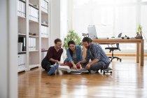 Трое креативных бизнесменов сидят на полу и смотрят в папку — стоковое фото
