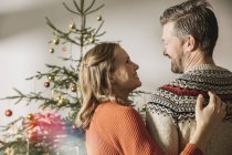Happy couple standing in front of Christmas tree — Stock Photo